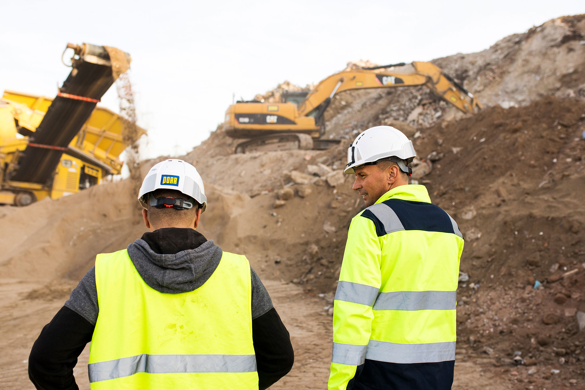 Photo: two employees in conversation; behind them, mountains of recycled construction waste, a conveyor belt and a track excavator at work